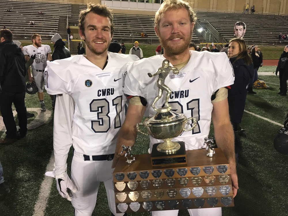 Photo of Cooper and Hunter Tulloch in their football uniforms holding a trophy