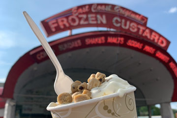 Photo of a cup of a cookie dough concrete in front of the East Coast Original Frozen Custard building's marquee-like sign