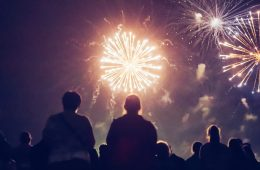 Photo taken from behind showing the silhouettes of people watching fireworks