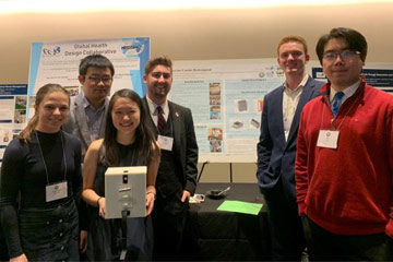 Photo of a group of students in Global Health Design Collaborative holding their vaccine carrier development in front of presentation posters