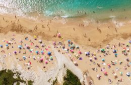Aerial photo of beachgoers with colorful towels and umbrellas on a beach near the sea