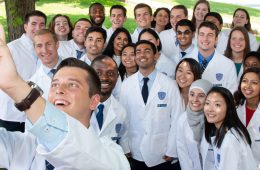 A group of new medical students pose for a selfie with their white coats on