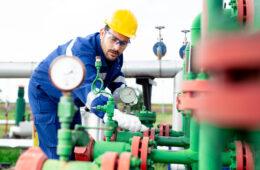 Worker adjusting gauge at oil refinery