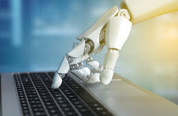 Robot hand typing on the laptop keyboard
