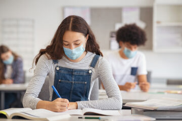 High school student taking notes from book while wearing face mask due to coronavirus emergency. Young woman sitting in class with their classmates and wearing surgical mask due to Covid-19 pandemic. Focused girl studying in classroom completing assignment during corona virus.