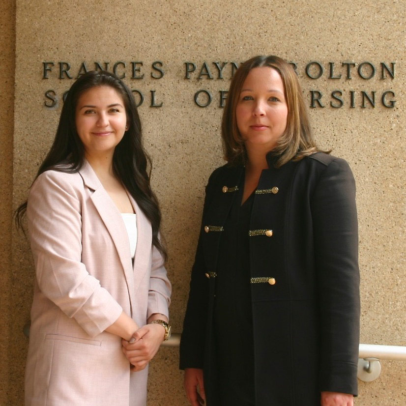 Photo of Estefania Hernandez and Stephanie Griggs in front of signage for the Frances Payne Bolton School of Nursing