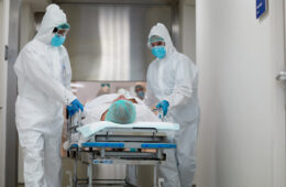 Photo of health care workers in PPE transferring a patient from the emergency area into the ICU