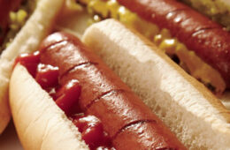 Close up photo on hotdogs with condiments on them