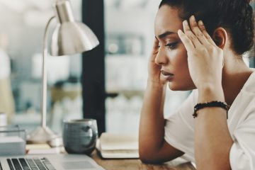 Photo of a young woman stressed out with her hands on her temples while sitting at a desk with a laptop