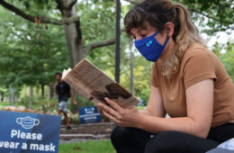"""Photo of a masked student reading a book on a bench next to a sign that says """"please wear a mask"""""""