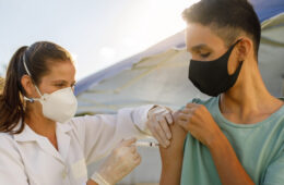 Photo of a health care professional administering a vaccine to a teenage boy while both wear masks