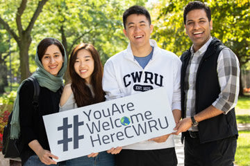 """Photo of four CWRU students holding a sign that says """"You Are Welcome Here CWRU"""""""