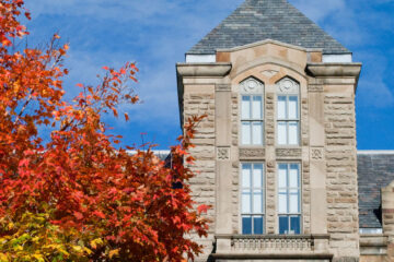 Photo of the top of Adelbert Hall with a tree with red leaves in the foreground