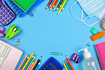 School supplies and COVID 19 prevention frame on a blue paper background