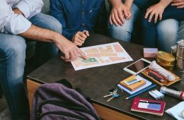 Close up photo showing a family sitting at their coffee table making an emergency plan with items to prepare nearby