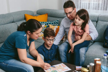 Photo of a family of four gathered around a table going over their emergency plan