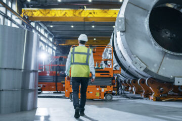 Following Shot of Heavy Industry Engineers Walking Through Manufacturing Factory. In the Background Professionals Working on Construction of Oil, Gas and Fuel Pipeline Transportation Products