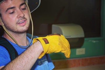 Photo of Shane Cooley holding a milipede on his gloved hand