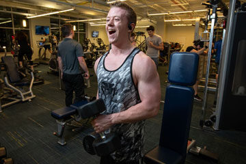 Photo of a CWRU student smiling while lifting weights