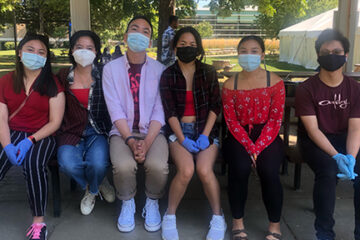 Filipino students sitting outside together and wearing masks
