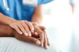 doctors hands on a patient's hands