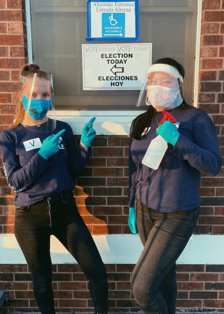 Photo of Vanessa Pilatova and Kiana Loo pose for a photo with masks, gloves and cleaning supplies outside a polling location on election day