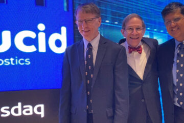 """Photo of the three Lucid Diagnostics founders posing for a photo in front of a digital sign that says """"Lucid Diagnostics"""" and """"Nasdaq"""""""