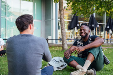 Photo of two men sitting on the ground outside in discussion
