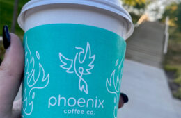 Photo of a hand holding up a to go cup of Phoenix Coffee