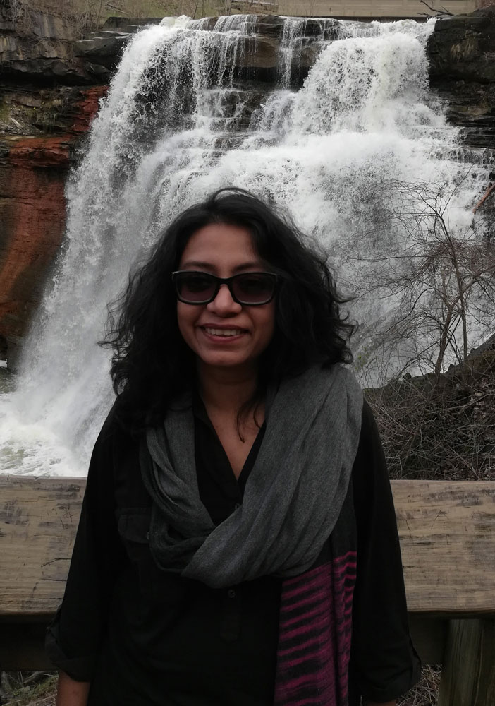 Photo of Reema Sen posing for a photo in front of a waterfall