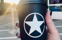 Photo of a hand holding up a Rising Star coffee to-go cup with sun beams shining down