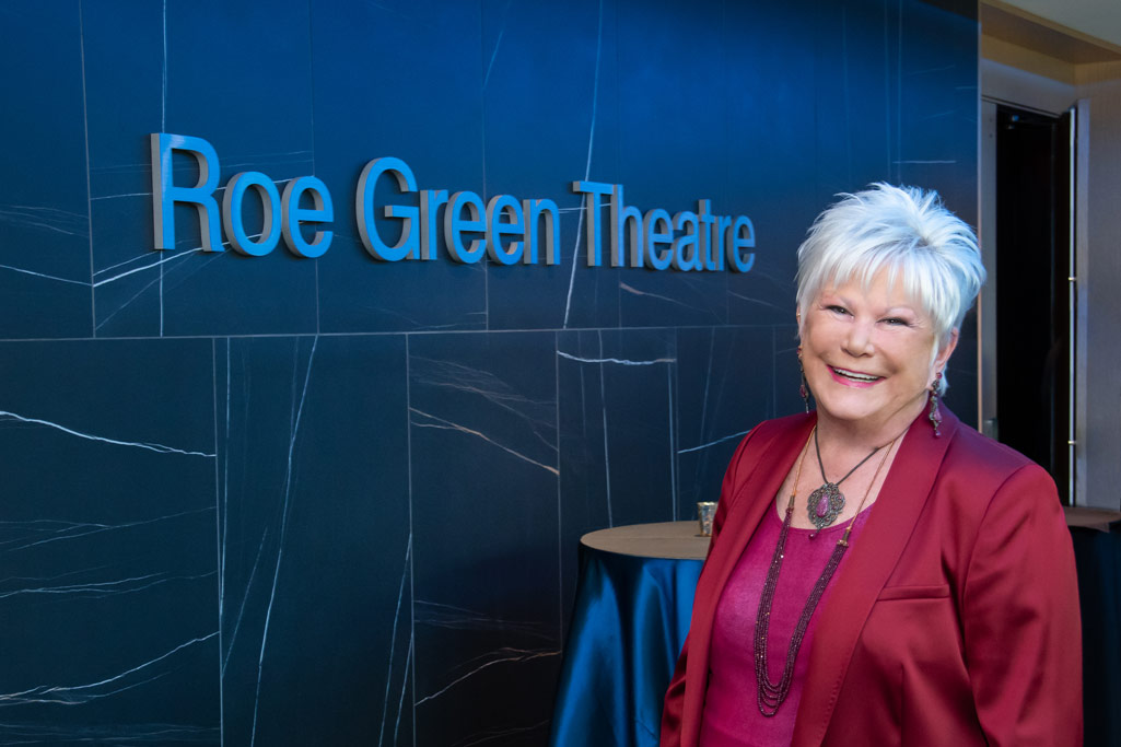 """Photo of Roe Green in front of signage that says """"Roe Green Theatre"""""""