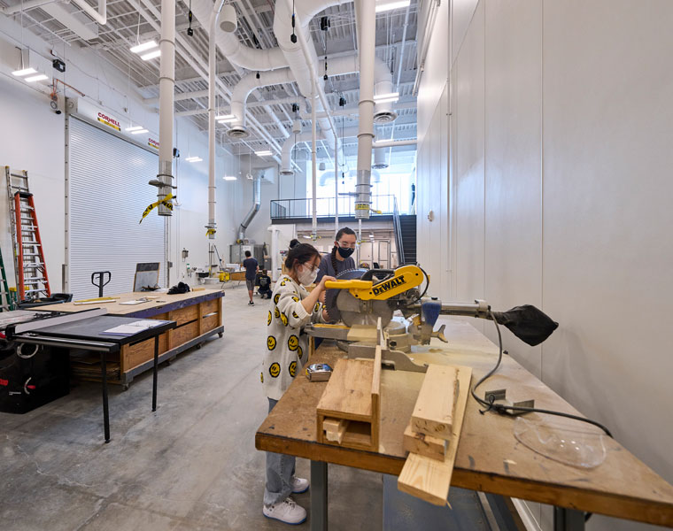 Photo of two students using a miter saw in the workshop